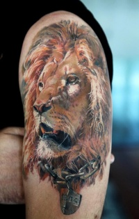 Lion in chains tattoo on arm